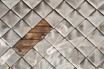 An einer Hauswand fehlen einige alte rautenförmige Zinkplatten