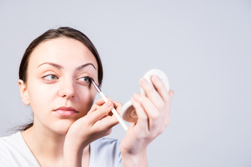Woman Applying Eyeliner While Looking at a Mirror