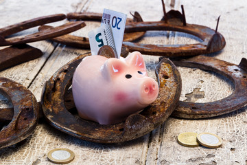 Sparschwein und Hufeisen auf Holz