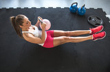 Fototapety Woman working on her abs with kettlebell