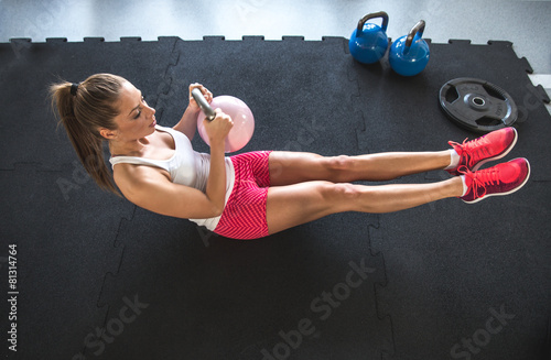 Poster, Tablou Woman working on her abs with kettlebell
