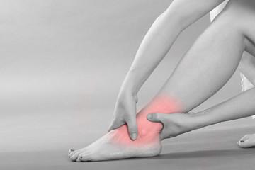 Sprunggelenk Schmerzen - schwarz weiß mit rotem Schmerzpunkt