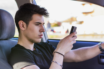 Distracted Young Man Using Cell Phone While Driving a Car