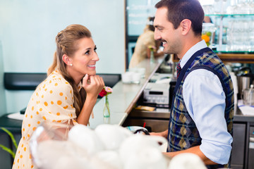 Girl in cafe or coffee bar flirting with barista