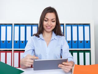 Lachende Geschäftsfrau im Büro mit Tablet