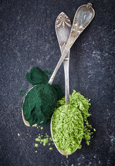 two spoons of spirulina algae and wheat sprouts powder