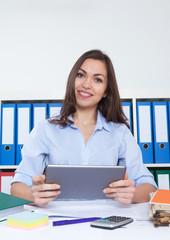 Geschäftsfrau im Büro mit Tablet schaut zur Kamera