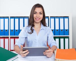 Fröhliche Geschäftsfrau im Büro mit Tablet