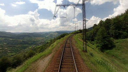 View along the railway in mountains from train driver cabin