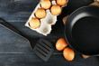 Still life with eggs and pan on wooden table, top view - 81319365