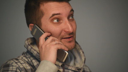 Young man talks on mobile phone on grey background