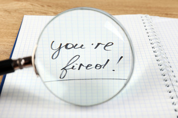 Message You're Fired through magnifying glass, closeup