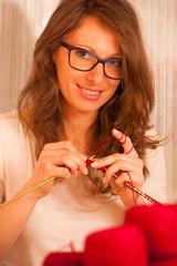 beautiful young woman knitting making handmade clothes