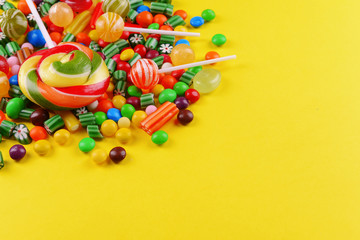 Colorful candies on yellow background