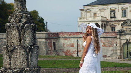 Blonde in a beautiful white dress and hat near the old castle.