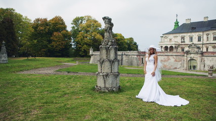 The girl in a white wedding dress near the castle on green grass