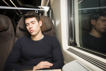 Young man sleeping while traveling on a train