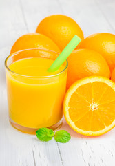 Orange juice and oranges with mint on white table