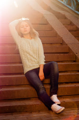 The girl with the sun in her hair sitting on stairs, toned