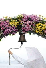 傘をさしながら花の鐘を鳴らす.