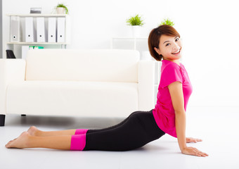 beautiful young woman stretching on the floor