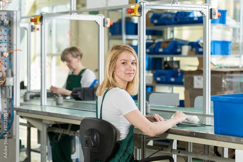 Femme travaillant sur la ligne de production Poster