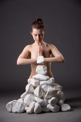 Meditating nude girl moves stones power of thought