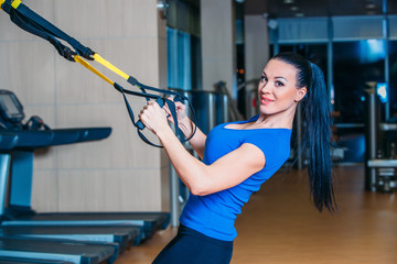 Young attractive woman training with htrx fitness straps in the