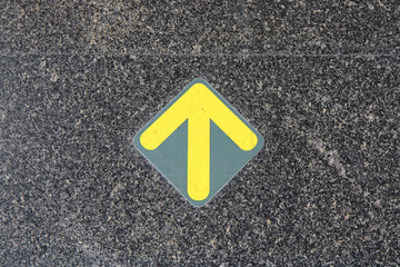 black cement floor with yellow direction arrow sign
