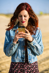 Young redhead woman with smartphone
