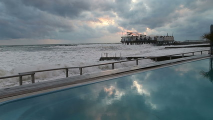 Pool with blue water on the beach in Sochi amid storm in the