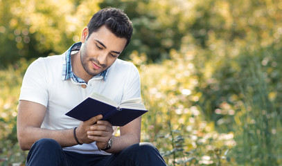 Student reading book in a park.