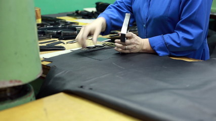 View of worker carves leather details for shoes