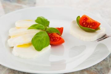 Mozzarellasalat mit Tomaten und Basilikum auf einer Gabel
