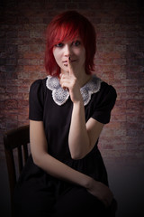 Red-haired girl sitting on chair calls for silence