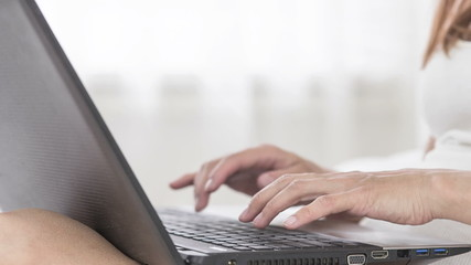 woman work at laptop in bedroom on the bed