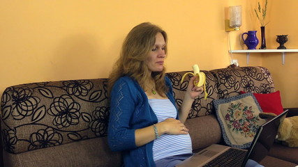 Pregnant girl eat banana work with computer and caress belly