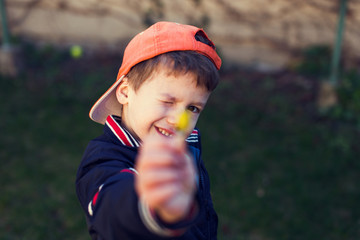 Little boy in cap showing yellow flower