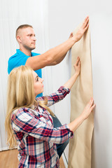 Young Couple Applying Wallpaper On Wall
