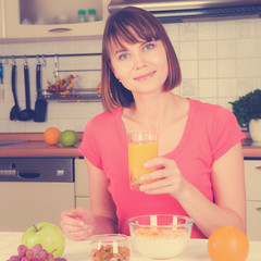 Young woman drinking orange juice with cereal muslin at home
