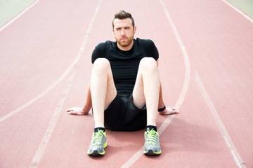 Man sitting on the running track