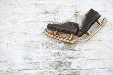 пара старых коньков на фоне стены