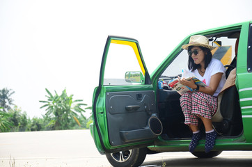 Thai woman portrait reading book in her car on street