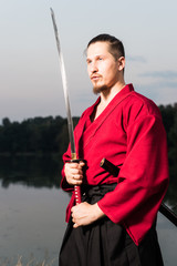 Man in ethnic samurai japanese clothing uniform with katana
