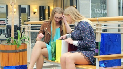 Two blondes sitting on a bench talking, bragging about their