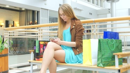 beautiful young smiling woman holding shopping bags and mobile