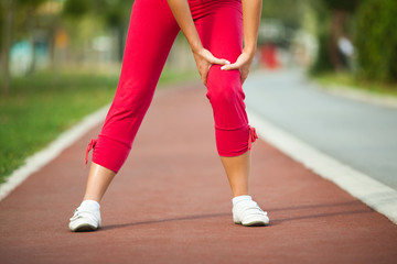Woman having pain in leg while jogging