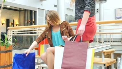 Beautiful blonde sitting on a bench Mall