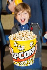 Portrait Of Excited Boy Offering Popcorn Bucket At Cinema