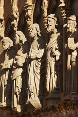 Ancient stone sculptures in a spanish cathedral portico. Olite,
